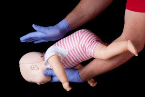 Doctor showing first aid for choking infant